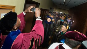 Meharry faculty take a photo backstage in full regalia.