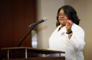 School of Dentistry Dean Cherae Farmer-Dixon, D.D.S., MSPH, uses an apple to illustrate a point while addressing new students in Meharry Medical College's School of Graduate Studies and Research. Dean Farmer-Dixon received her Master of Science in Public Health degree from Meharry's School of Graduate Studies.