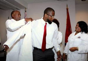 Meharry President James E.K. Hildreth, Ph.D., M.D., helps new dental student Fabian L. Fuller II with his new white coat as the dean of the School of Dentistry, Cherae Farmer-Dixon, D.D.S., MSPH looks on.