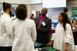Two recruiters have a conversation with Meharry students.