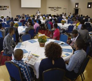 Over 100 young black men sit at tables and listen to a speaker.