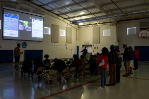Meharry students present to Haywood Elementary educators in a darkened gym.
