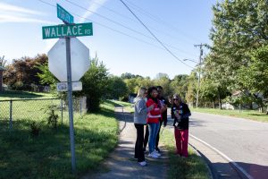 A volunteer group stands at an intersection next to a street sign.