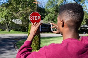 A Meharry student photographs a stop sign with his phone.