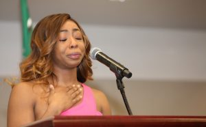 Medical student holds back tears while speaking at a podium.
