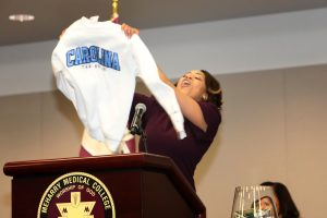 Medical student holds up sweater with her match's logo at the podium.