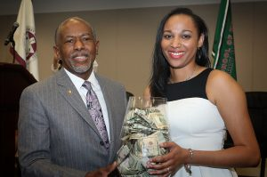 Dr. Hildreth posses with student who has won a vase full of money in a drawing.