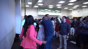 Medical students and celebrate their matches in a large crowded room.