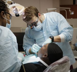 Meharry students examine patient's teeth in a dentist's chair.