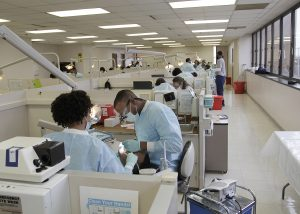Room filled with dentist stations occupied by patients and Meharry students.